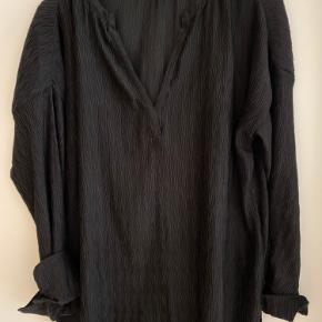 Bluse fra Rabens Saloner i crepe kvalitet. 100% polyester. Over bryst 70 cm.  68cm foran i længde og 78cm bagpå i længde.