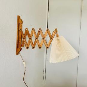 Flot og eftertragtet sakselampe i lyst olieret træ med nedadvendt fatning og afbryder på kablet. Den fleksible arm på sakselampen kan trækkes ud til en længde 78 cm og den nedadvendte fatning betyder, at selve skærmen er placeret under armen.  Med sakselampen får du en yderst fleksibel væglampe hvor lyset kan placeres efter behov.  Meget æstetisk tiltalende og elegant udseende. Monteringsplade 4 x 3 x 35 cm. Fuld udslået længde 78 cm. Sammenfoldet længde: 18 cm Skærmen fremstår noget medtaget, men kan medfølge uden beregning.