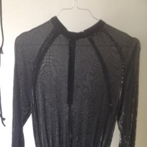 Virkelig smuk vintage/retro kjole i glitter sort viskose i 1950'er stil. Dansk design og har et metallic look. Det er en smule svært at se på billedet, men stoffet har striber af sølv over det hele. Kjolen er gennemsigtig fra taljen og op og for neden et underskørt. Ærmerne er trekvart og kjolen lårkort. Den er elastisk og sidder derfor utrolig flot! Er en str 36 men passer også en lille 38.   Den perfekte nytårskjole! 🍾 eller til julefrokost