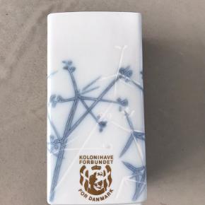 Vase fra Royal Copenhagen i hvid og blå - Kolonihave forbundet for Danmark..  - Porcelæn - 22785N - 2145785 - 18 x 6,8 x 9,2 cm  - Befinder sig i Aalborg sø