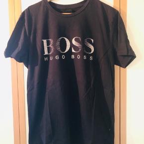 Behagelig T-shirt med stort print for fra Hugo Boss sælges pga pladsmangel.  T-shirten fremstår i perfekt stand da den højest har vært i brug 3-4 gange siden den blev købt. Har ingen former for pletter, huller eller ander former for slitager.  Kom med et fair bud