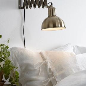 Sakselampe/væglampe i messing fra Ellos i modellen Edgar - står som ny uden skader og ridser.   Lampen har en fleksibel, drejelig og udtrækkelig arm. Arm kan trækkes ud fra 15 cm til 58 cm.   Skærm Ø 18,5 cm. Højde 30 cm. E27. Max. 40W