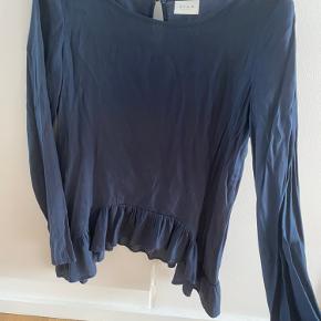 Flot bluse med flæse i bunden, der går længere ned i begge sider end foran og bagpå  Kan afhentes i Odense C eller sendes på købers regning
