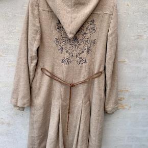 Dejlig overgangsfrakke fra Vero Moda i str. L. Lidt længere bagpå med fede detaljer på ryggen. Den kradser overhovedet ikke..  Den er gået lidt op i syningen forneden (se billede) men det kan nemt lige sys i hånden. Bæltet lidt slidt nogle steder, men kan tages af og jakken kan bruges uden eller evt. med sit eget bælte..  Ellers er jakken i rigtig fin stand.. vaskeanvisning og materiale (se billede)  Befinder sig i Tarup - Odense NV
