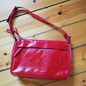 Smuk rød håndtaske i kalveskind. Mål: 28x18x7. 1 lynlås rum med klap på forsiden, 1 lynlås rum på bagsiden, 1 lynlåsrum indeni og mobil-, kuglepen- og lille lomme indeni. Prisen er inkl forsendelse