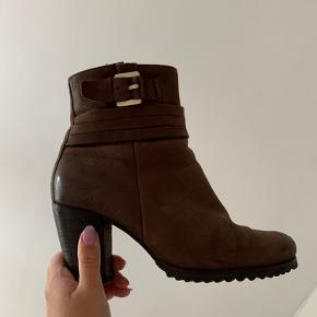 Smuk støvle fra Ecco. Perfekt til vinterbrug da den er foret. Der er små brugsspor i foret, men det gør intet for komforten. Se billede 5 for yderligere brugsspor. Skoen er blevet omhælet, og er næsten ikke brugt derefter, så hælen fremstår som ny. Hælen er 7,5 cm på højeste sted. Ægte læder.  #læder