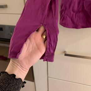 Farven er fuchcia. Vasket en del gange, hvilke har forstærket det slidte look. Fin detalje ved ærmerne, se foto. Polyester.