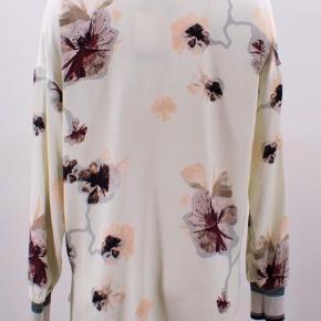 Smuk skjorte i glat satin fra By Malene Birger med aftageligt tørklæde. Skjorten er lavet i et smukt print, har slids i siderne og ribstrikket manchetter med diskret glitter.  Detaljer: Aftageligt tørklæde Pasform: Normal Kvalitet: 100% Polyester Mærke: By Malene Birger Model: Isabela