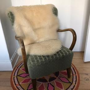Fin lænestol i grøn farve. Træben, træ-armlæn. God fjerding stadig, er dog lidt slidt i betrækket, derfor følger lammeuldskinnet med.