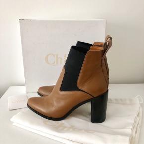 Chloé støvler i læder og elastisk med 9 cm hæl.  Æske, dustbag og kørt følger med.  Nypris: 5400 kr. Mindstepris: 1600 kr.  Der er desværre et mærke på indersiden ag hælen, som vist på sidste billeder. Dette skyldes, at jeg har stødt hælen på modsatte støvle på, og den mørke kant på hælen har derved lavet mærker. Jeg ved ikke, om det kan fjernes, hvis man tager støvlerne på hælebar.  Ingen bytte!  Kan afhentes på Nørrebro eller sendes på købers regning. Jeg handler via mobilepay.