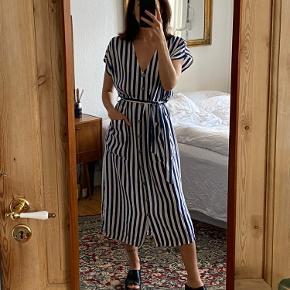 Flot Rude kjole med hvid/blå striber. Fitter onesize alt efter ønsket fit. Har lommer og bindebånd i taljen. Har en lille 'skramme' på forsiden, se billede.