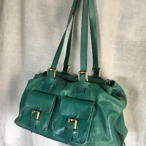 Fra WHITE FLIRT : Skind taske i fed farve - grøn med lilla satin foer. Masser af rum og lommer - virkelig rummelig taske.  3 Store rum. To skulderremme og en lang rem til cross-body. Ikke med på billeder - taget af og ligger i tasken. Lilla satinfoer.  Lidt brugstegn / slid i hjørnerne i bunden som eneste brugstegn. Højde : 25 cm. Bredde : 42 cm. Dybde : 20 cm. Oprindelig købspris : 1800,- Sender gerne på købers regning.
