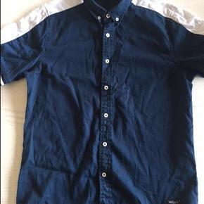 Varetype: Blå Hvid Kortærmet skjorte - str. M Farve: mørke blå med hvid kant  Rascals - Blå Hvid Kort ærmet skjorte i smart design - str M    Ærmelængde indvendig : 11 cm Ryglængde : 75 cm  100 % Cotton  INGEN HUSDYR & IKKE RYGER HJEM.  Vægt 300 gr.  Samler gerne flere køb i en forsendelse  Sendes med Dao365 til nærmeste udleveringsted , medmindre andet aftales
