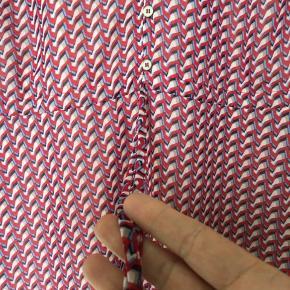 Sød bluse i 100% polyester chiffon. Den har en løbegang i taljen som man kan stramme lidt ind. Den er i 2 lag, og derfor ikke gennemsigtig.