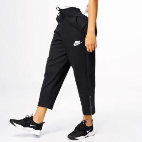 Oprindelig pris: 499 Stand: Brugt en gang Farve: sort Str. XL/40  Nike Sportswear AV15 Sneaker Pant til kvinder. Bukserne er bløde og lækre fra første gang du hopper i dem, og giver dig en dejlig føling dagen lang. Taljen er med snøre så du kan tilpasse dem til det rigtige fit, mens af de korte ben giver plads til en masse fokus på dine sneakers. Deraf navnet på bukserne. Buksekanten er med lynlås så du også her kan tilpasse fit og ventilation til kroppen. Bukserne fuldendes af de lommer der gør plads til sikker opbevaring.