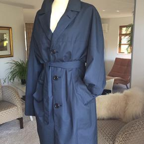 Denne utrolige smukke, unikke og yderst velholdte skræddersyet vintage cottencoat med lækre detaljer både inde i frakken og uden på.  Frakken er unisex. Bæltets fine detaljer er skræddersyet til aldrig at blive tabt + at det får frakken til at sidde virkeligt smukt. Forret er stilfuldt udført og får frakken til at falde naturligt. Skuldrene er syet med en smuk blød runding, og frakkens længder er lige over knæet. Det er en mandefrakke, men jeg har brugt den som en str. 38/40 da jeg personligt mener at den fremføre sig bedst, som set på billed 1 og 2.  Længde: 100 cm Bryst: 120 cm Ærme: 62 cm