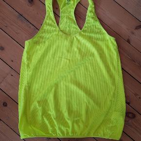 Neongul træningstop med bryderryg i 100% polyester. Elastik ved bundkant.  Mål Længde: 72cm Bredde: 50cm Bundkant: 49cm