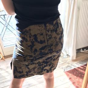 Unik guld printet nederdel på mørkeblåt tekstil.