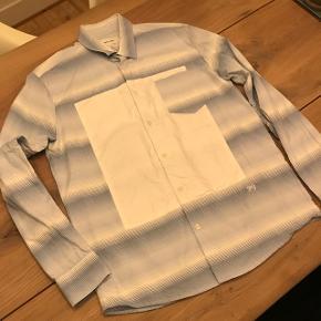 Flot stribet Soulland skjorte med hvid firkant på midten:) brugt få gange og fejler derfor ikke noget.Nypris: 1500kr Kan sendes på købers regning.