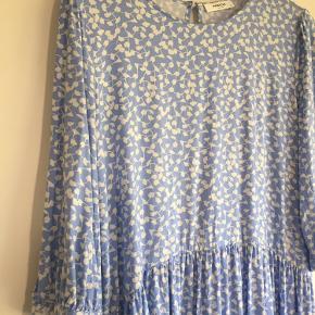 Fin knælang lyseblå kjole. Rund halsudskæring, knap i nakken, 3/4 lange ærmer og løs pasform. Længde 100 cm, omkreds bryst 100 cm.