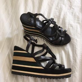 Super flotte kilehæle, meget nemme at gå i. Der er syet en ekstra rem på, men kan stort set ikke ses når skoen er lukket.