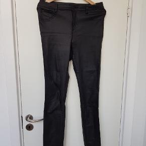 Sorte jeans/jeggins i str. Xl med et lidt skinnende materiale så det efterligner læder. Der er stræk i.