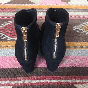 Sofie Schnoor Ankelstøvler i sort ruskind, med gylden lynlås bag på. Kile/plateauhæl. Hælhøjde 8 cm, men 1,7 cm plateau gør dem super behagelige at have på. Kun prøvet på hjemme. Ny pris 2200kr🙈