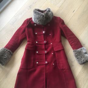 """Flot mørkerød frakke fra Karen Millen med """"pels"""" på ærmer og krave. Den sidder super flot til kroppen. Det er str. UK10. Prisen er fast og ved afhentning, hvis den skal sendes tillægges 60 kr."""