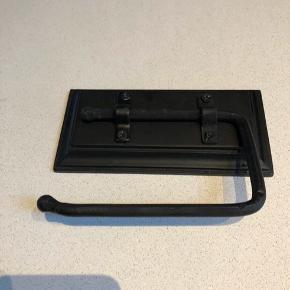 Toiletrulleholder i sort træ med sortmalet metal. Den er rustik i udtrykket og rigtig fin. Aldrig brug
