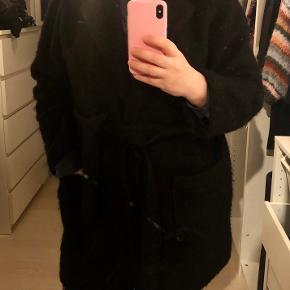 Byd gerne ☺️ Fenn Coat i sort fra Ganni er en klassisk frakke, der går ned til lige over knæet. Frakken er lavet i en uldblanding med tekstur og et aftageligt bælte. Der er påsatte, dybe lommer og stumpeærmer.   - Lavet af 50% uld og 50% polyester.
