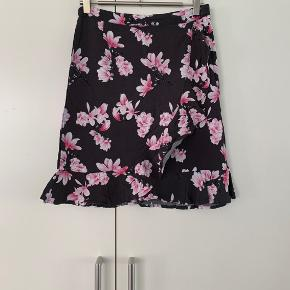 Super pæn nederdel med lyserøde blomster. Har i venstre side en skjult lynlås. Foran har den flæser, som den også har hele vejen rundt i bunden Måler 50 cm