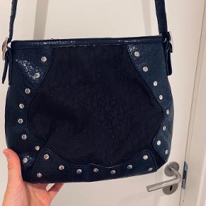 Sort DKNY taske med nitter og læder rundt i kanten. Lukkes med lynlås og lang justerbar rem.  Pæn stand - intet slids  Køber betaler porto.