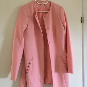 Smuk frakke til salg! Den er fersken farvet, og har en lille plet på ryggen, som ikke er vildt tydelig at se. Jeg ved ikke om det kan vaskes af, da jeg ikke har vasket frakken med det på.
