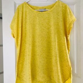 Lækker og let t-shirt fra ICHI i flot gul farve med let glimmer. Lidt længere bagpå. Lige op og ned model med god plads. Brystmål: 60 cm foran og det samme bagpå Længde: 67 cm  *Kom også gerne med et bud*