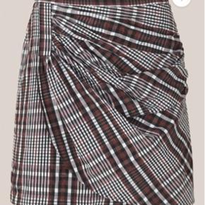 Denne korte nederdel er fremstillet i en bæk og bølge-kvalitet bestående af bomuld og polyester. Nederdelen har fast linning med skjult lynlås på bagsiden, og fronten prydes af et asymmetrisk stykke med små rynk, som giver nederdelen kant.