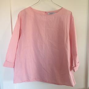 Fin skjorte/bluse i lyserøde og hvide striber. 3/4 ærmer. Har selv syet en knap i nakken hvor den lukkes, da den ellers gik op, men den ses ikke. Kun brugt enkelte gange