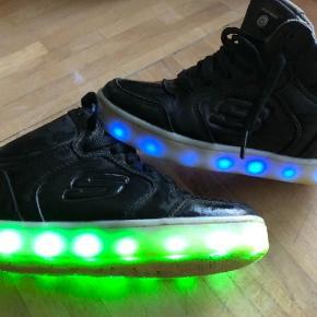 Super fede sko med LED-lys, der kan lyse og/eller blinke  Man tænder for skoene og kan også slukke for lyset igen. Der kan vælges mellem 8 forskellige farver, hvoraf nogle af variationerne skifter farve hele tiden  Skoene oplades via medfølgende oplader og kan dermed bruges igen og igen   Sneakers Farve: Sort Oprindelig købspris: 600 kr.