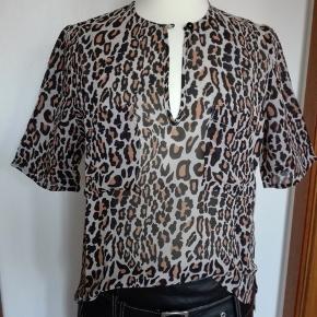 Blusen har en knap i halskanten, med lille slids ned.  Måler 54 cm. foran og 60 cm. bagtil. Halv silke, halv viskose.  Mp. 350 pp. Bytter ikke  Mobilepay foretrækkes  Bluse Baum und Pferdgarten Farve: Leopard