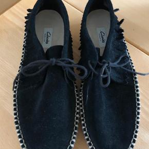 Varetype: Hyttesko Farve: SORT Oprindelig købspris: 950 kr.  Meget lækker Clarks hyttesko med frynser i sort ruskind.  En anvendelig sko med fin gå Comfort