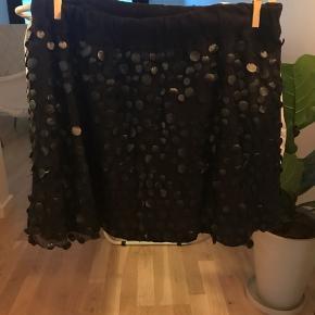 "Nederdel med ""palietter"" i læderlook. Carmakoma str. S. Taljemål: 90 cm. Elastik i taljen. Længde: 48 cm."