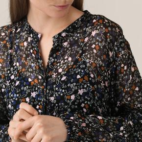 Denne maxikjole er fremstillet i en let transparent viskosechiffon med blomstret all-over print med tilhørende underkjole i viskose. Kjolen har en delikat krave med synlig knaplukning ned til taljen, hvorfra kjolen får vidde og flow. Ærmerne har en smule volumen og elastik ved håndleddet.  100% Viskose