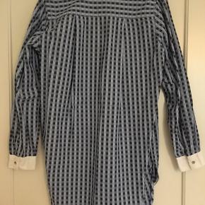 Fin skjorte i blåt mønster og m hvide kanter. Længere model, ned over bagdelen.