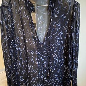 Flot gennemsigtig blåmønstret bluse med frynset krave og ærmer og snore om halsen.