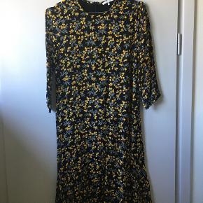 Fin kjole med blomsterprint. Går til lige over knæet