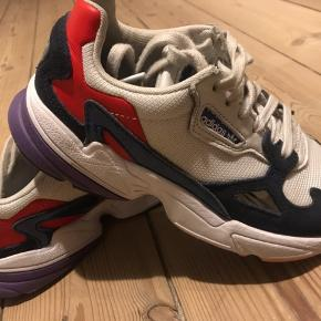Falcon adidas i hvid og navy. Standen er egentlig rigtig god, men det da er en hvid sko, skal man jo ikke gå mange gange i den, før man kan se det lidt. Desuden er der gået meget lidt af den lilla farve nederst på sålen på den ene sko, hvilket fremgår af billede nr 2. Ellers er skoene i super stand  Skoenes størrelse er 39 1/3!   Nypris: 800  Salgspris: 475 ekls fragt  Hvis du vil sparre fragten, kan vi mødes i københavn og handle.