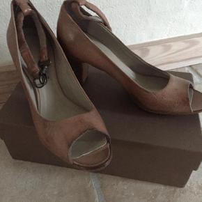 SILVANO SASSETTI Pumps heels peeptoe, lys brun 3900 kr. SILVANO SASSETTI  Luksuriøst italiensk håndværk fra Silvano Sassetti  Silvano Sassetti er et anerkendt førende luksusbrand i håndlavede sko og støvler.   Sassetti-skofabrikken ligger i Monte San Pietrangeli, hvor Silvano Sassetti grundlagde sin virksomhed i 1977, efter i mange år at have arbejdet som lokal skomager i sit hjem i Italien.   Håndsyede Peeptoe pumps i den smukkeste håndværk med et råt udtryk.  7 cm synlig hæl ( højde i alt med indvendig hæl i alt 8 cm. Skoen er til den smalle side.