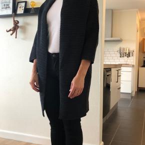 Dejlig mørkegrå cardigan i merino uld fra Sibin Linneberg. Cardigan er strikket i et stribet mønster og har lommer i siderne. Den kan både bruges som overgangsjakke og som almindelig cardigan.