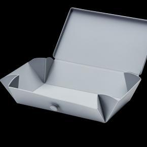 Uhmm No. 01 Light Grey Box/Dark Grey Strap ALDRIG BRUGT - KUN VASKET Uhmm Box er en moderne opbevaringsboks, som er nem at folde ud til en flad tallerken, der let kan gå i opvaskemaskinen, mikroovn og fryser. Uhmm Box er produceret i Danmark og naturligvis 100% fri for alle usunde parabener og ftalater, der kan overføres til maden.  Box: Materiale: Polypropylen – et giftfrit, lugtfrit og fødevaregodkendt plastmateriale. Farve: Grå Størrelse: 10x18x5cm Foldetestet 1000 gange  Bånd: Materiale: Silikone, der er fødevaregodkendt, og som kan gå i opvaskemaskinen, mikroovn og fryser. Farve: Grå Størrelse: 36x2x0,2cm