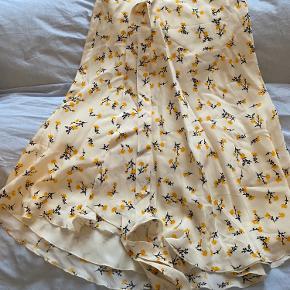 Flot silke nederdel i wrap-stil med bindebånd k taljen. Lidt kortere foran end bagtil. Går til ca lidt over knæene.