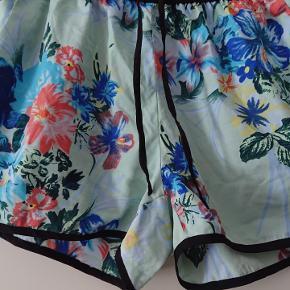 Flottemultifarvede, blomstrede, VILA shorts med snøre i livet, i str M. Sidelommer. 100% polyester. Meget kort model.